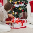 Woman putting present box under Christmas tree — Stock Photo #16778399