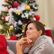 Dreaming young woman sitting near Christmas tree — Foto de Stock