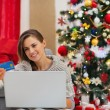 Happy young woman making online purchases near Christmas tree — Stock Photo