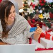 Smiling woman with laptop and credit card near Christmas tree — Stock Photo #16778447