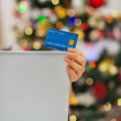 Closeup on credit card and laptop in front of Christmas tree — Stock Photo