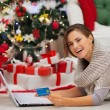 Happy woman with laptop near Christmas tree making online purcha — Stock Photo #16778497