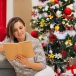 jonge vrouw lezen boek in de buurt van de kerstboom — Stockfoto #16778717