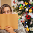 Woman hiding behind book in front of Christmas tree — Stock Photo