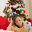 Woman reading book near Christmas tree — Stock Photo