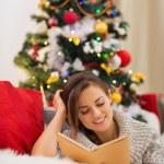 Woman reading book near Christmas tree — Stock Photo