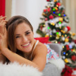 Smiling young woman in pajamas laying on sofa near Christmas tre - Stock Photo