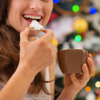 Closeup on young woman eating cookies with hot chocolate near Ch — Stock Photo #16779333