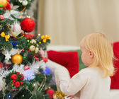 Baby decorating Christmas tree. Rear view — Stock Photo