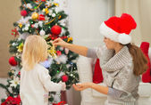 Mother and baby decorating Christmas tree — Stock Photo