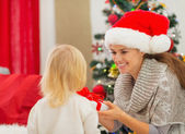 Mother presenting baby girl Christmas present — Stock Photo