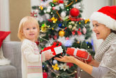 Mother and baby girl changing Christmas presents — Stock Photo