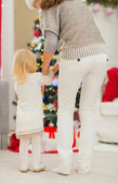 Baby and mother in front of Christmas tree. Rear view — Stock Photo