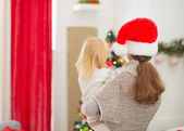 Mother holding baby and looking on Christmas tree. Rear view — Stock Photo