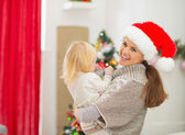 Mother holding baby in front of Christmas tree — Stock Photo