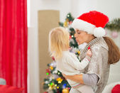 Mother kissing baby in front of Christmas tree — Stock Photo