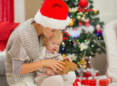 Young mom and baby girl playing near Christmas tree — Stock Photo