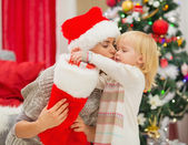 Mother kissing baby taking out present from Christmas sock — Stock Photo