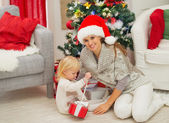 Baby sitting near mother and open Christmas present box — Stockfoto