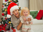 Portrait of laughing mother and eat smeared baby near Christmas — Stock Photo