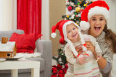 Portrait of mother and eat smeared baby in Christmas hats near C — Stock Photo