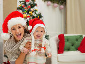 Portrait of mom and eat smeared baby girl in Christmas hats near — Photo