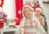 Portrait of eat smeared baby girl in Christmas hats dancing — Stock Photo