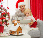 Mother showing baby something in tablet PC near Christmas tree — Stock Photo