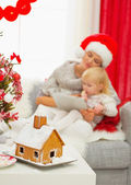 Closeup on Christmas Gingerbread house and mother and baby girl — Stock Photo
