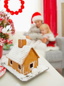 Closeup on Christmas Gingerbread house and mother and baby using — Stock Photo