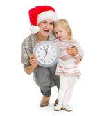 時計を保持している、クリスマスの帽子と赤ちゃんの女の子の幸せな母 — ストック写真