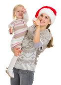 Smiling mother in Christmas hat and baby girl pointing up on cop — Stock Photo