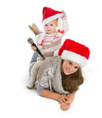 Baby girl in Christmas hat with microphone sitting on mother bac — Stock Photo