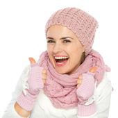 Donna sorridente in maglia sciarpa, cappello e muffole rivelando i pollici — Foto Stock