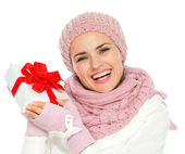 Happy young woman in knit winter clothing holding Christmas pres — Stock Photo