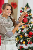 Happy young woman holding Christmas ball near Christmas tree — Stockfoto