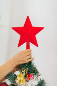 Closeup on woman hand decorating Christmas tree with topper — Stock Photo