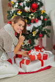 Woman putting present box under Christmas tree and showing shh g — Zdjęcie stockowe