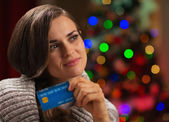 Portrait of thoughtful woman with credit card in front of Christ — Stock Photo