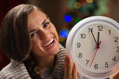 Portrait of smiling young woman showing clock in front of Christ — Stock Photo