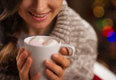 Closeup on hot chocolate with marshmallows in hand of happy girl — Stock Photo