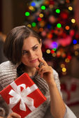 Thoughtful young woman with Christmas present box — Stock Photo