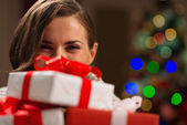 Girl hiding behind Christmas present boxes — Stock Photo