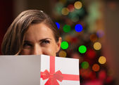 Girl hiding behind Christmas postcard — Stock Photo
