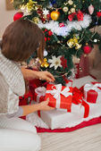 Woman putting present box under Christmas tree — Stock Photo
