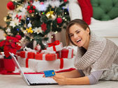 Happy woman with laptop near Christmas tree making online purcha — Stock Photo