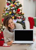 Femme heureuse à la recherche d'écran blanc ordinateur portable près de sapin de noël — Photo