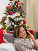 счастливый молодая женщина, выступая мобильных возле елки — Стоковое фото