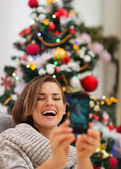 Happy woman near Christmas tree making self photo — Stock Photo