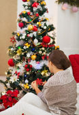 Woman sitting near and decorating Christmas tree. Rear view — Stock Photo